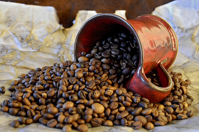 Brown coffee beans with red ceramic mug