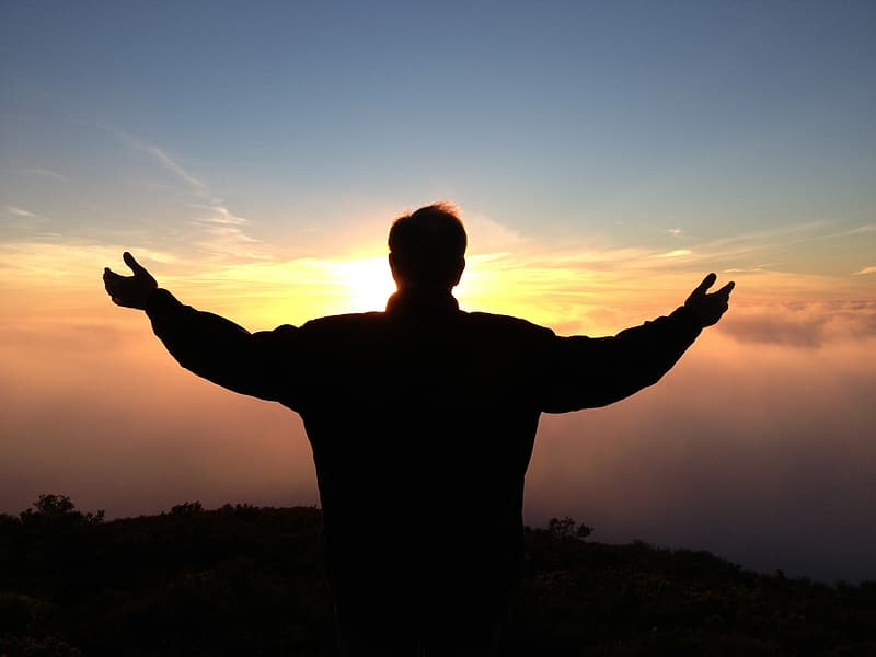 Silhouette of man standing spreading his hand during golden hour