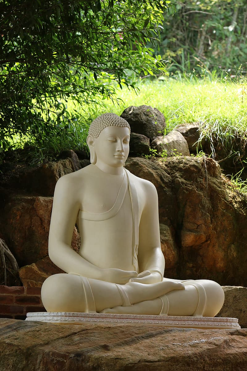 Woman in white pants sitting on brown rock