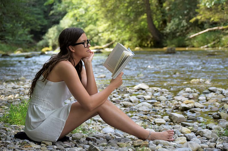Woman in white dress sitting on rocky shore reading book during daytime