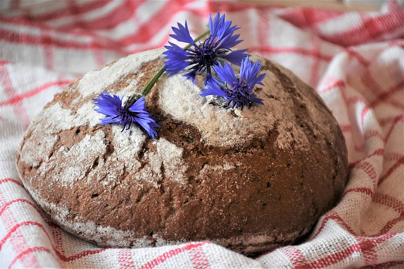 Brown round cake with blue flower on top