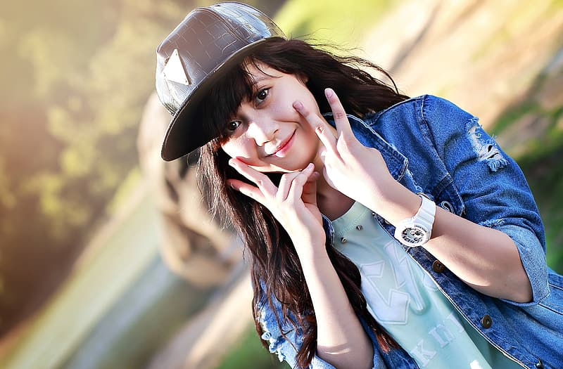 Woman wearing blue denim jacket and black hat posing during daylight photography