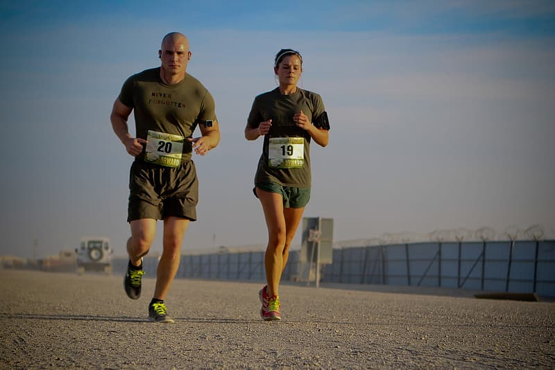 Man and woman in green shirt and shorts running during daytime