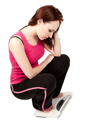 Woman wearing pink tank tank and black pants on digital personal scale