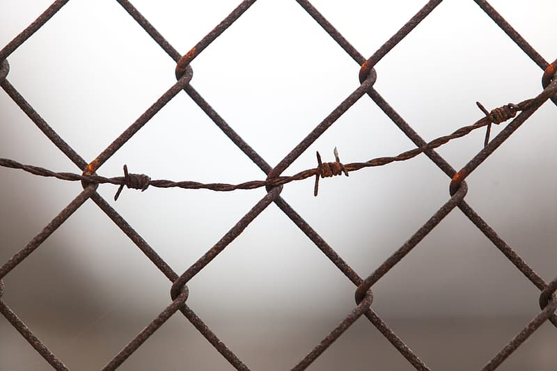 Black metal fence with barbwire