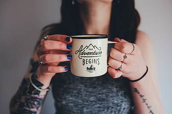 Closeup photography of person holding white the adventure begins printed mug