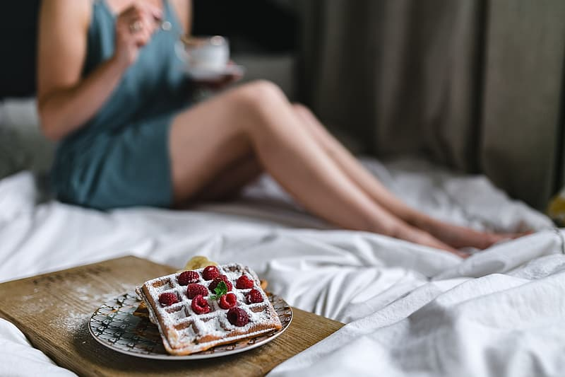Woman in blue dress sitting on bed with strawberry on top