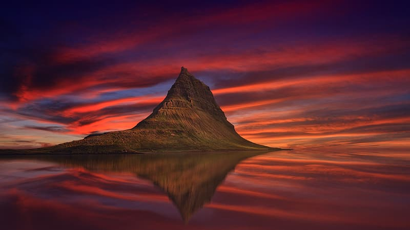 Brown mountain with reflection on water