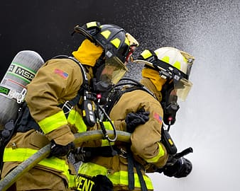 Two firefighter carrying fire hose