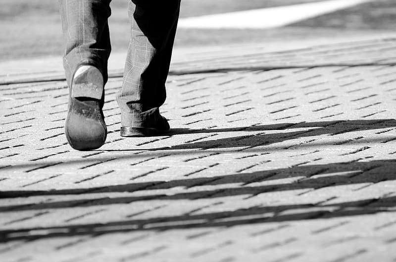 Person wearing pair of black shoes while walking on gray pavement