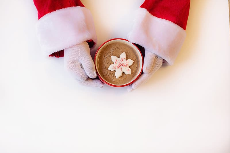 Person holding red ceramic mug with coffee