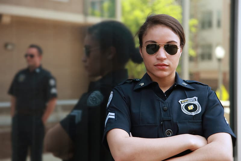 Woman in black suit wearing sunglasses while leaning on wall