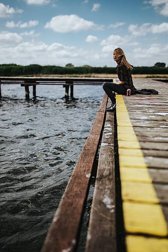 Woman in black jacket and pants standing on wooden dock during daytime