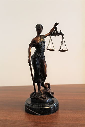 Person holding balance scale figurine on brown wooden surface