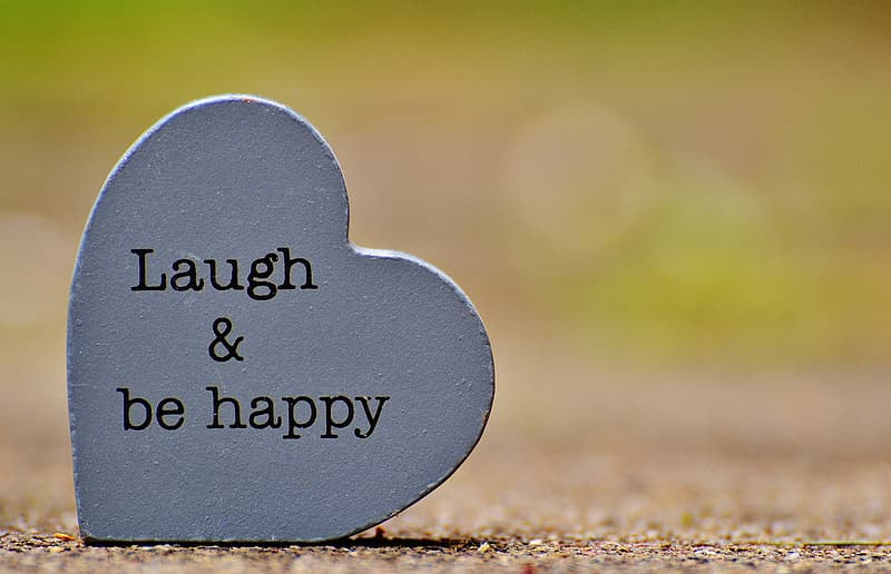Laugh & be happy text on heart-shaped gray concrete decor