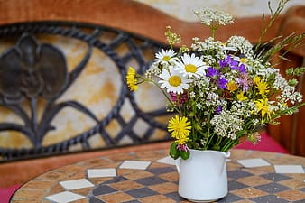 Assorted-color flowers in white vase on table