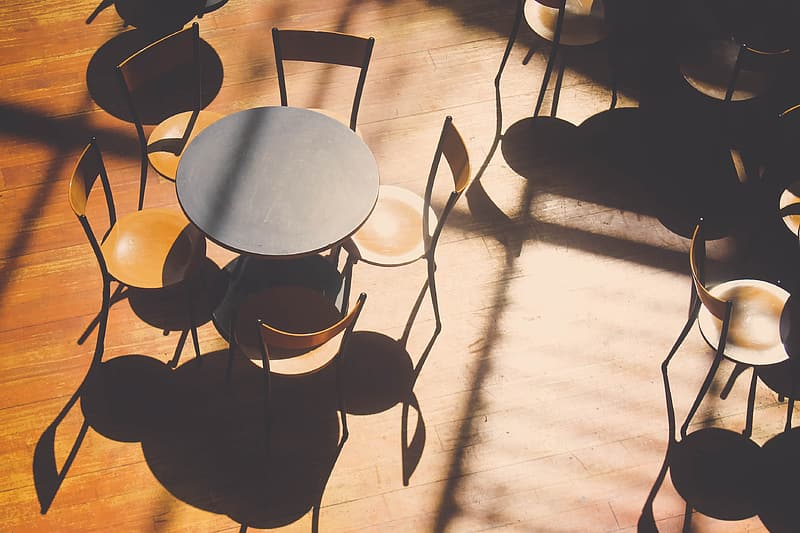 Five brown wooden chairs arranged around black wooden table