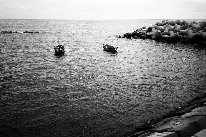 Grayscale photo of people riding on boat on water