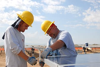 Two men in yellow hard hat helmets installing solar panels during daytime