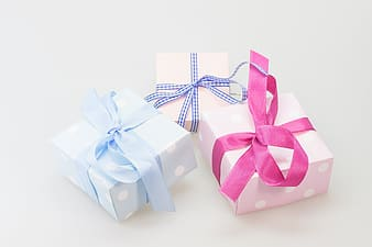 Three assorted-color wrapped gifts on white surface