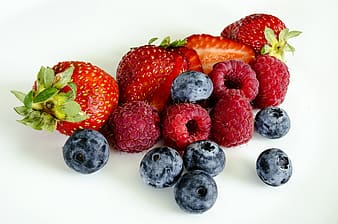 Grasp berries, blueberries, and strawberries on top of white surface