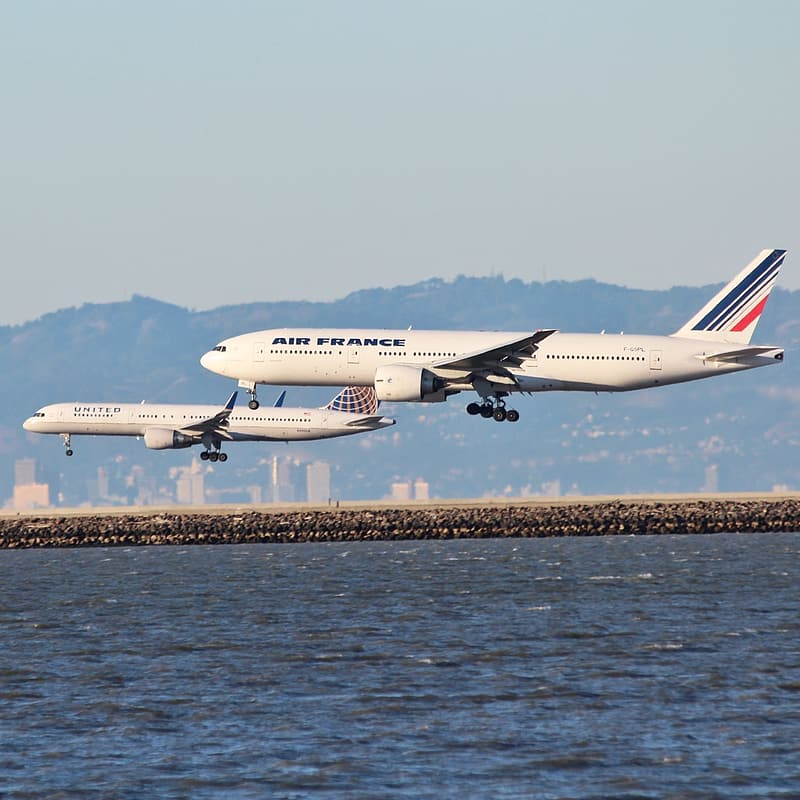 Air France airliner flying beside another airliner above water at daytime