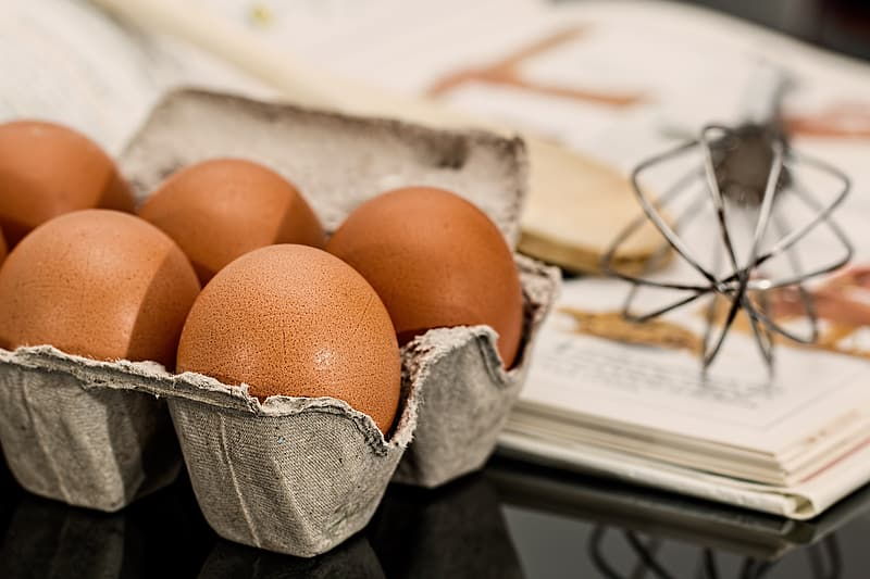 Tray of brown eggs beside gray whisk