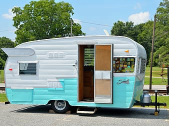 Teal and white travel trailer in concrete road