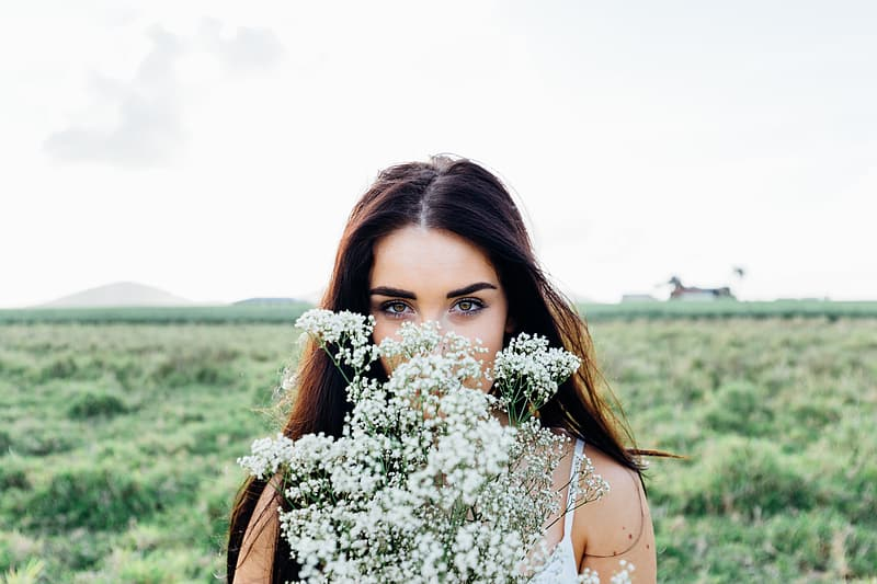 Shallow focus photography of woman holding white petal flower