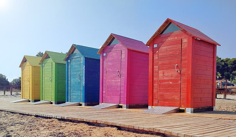 Five multicolored outdoor toilet booths