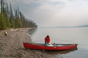 Person in red hoodie stands next to red rowboat photo during daytime