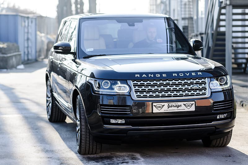 Black Land Rover Range Rover SUV running on road during daytime