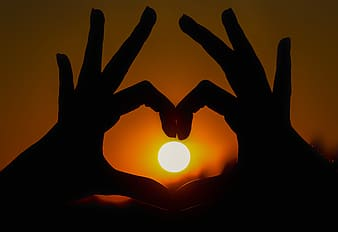 Silhouette of heart shaped hand gesture