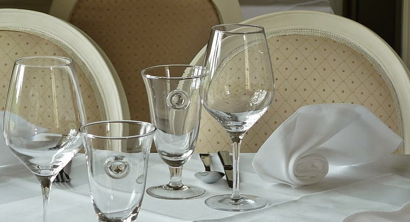 Four wine glasses on white table curtain close-up photo