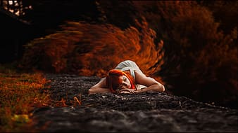 Red-dyed haired woman in white dress lying on ground