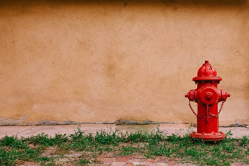 Red fire hydrant beside brown wall