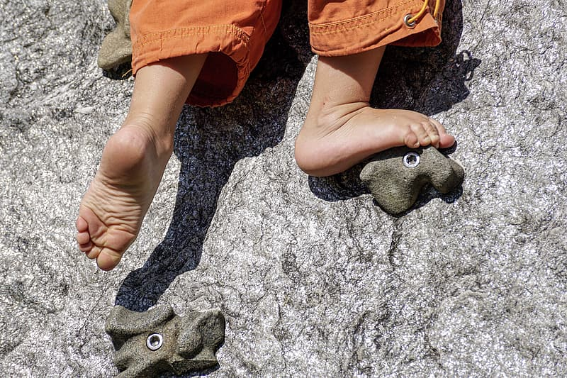 Person in orange pants holding gray stone