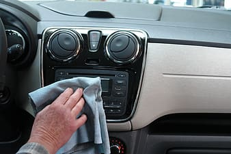 Person wiping the car stereo of his car