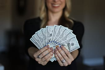 Woman holding fan of us dollar bill