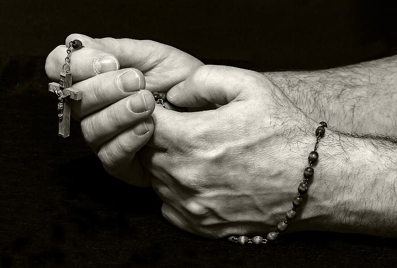Grayscale photography of person holding rosary