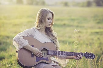 Shallow focus photography of woman playing cutaway acoustic guitar