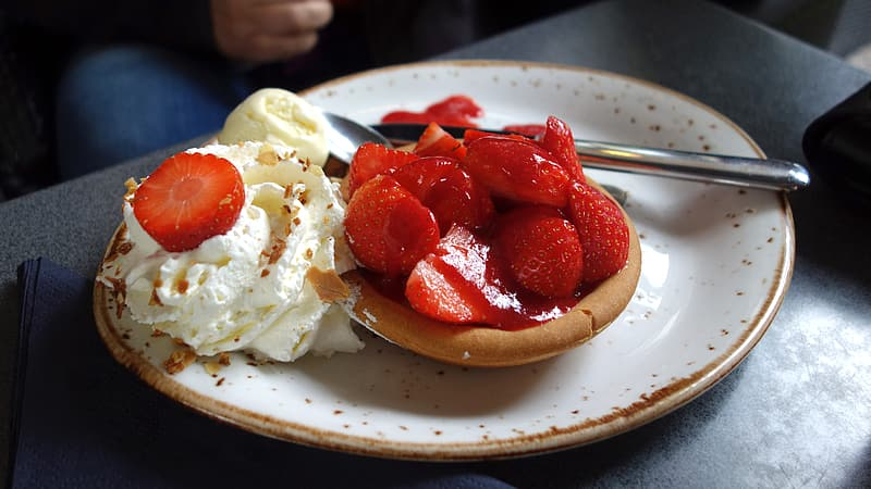 Strawberry on brown bread on white ceramic plate