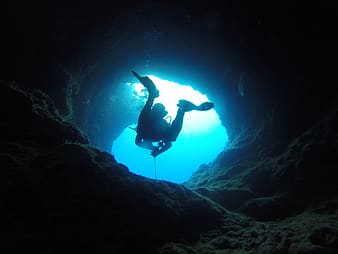 Person in scuba diving suit in cave underwater