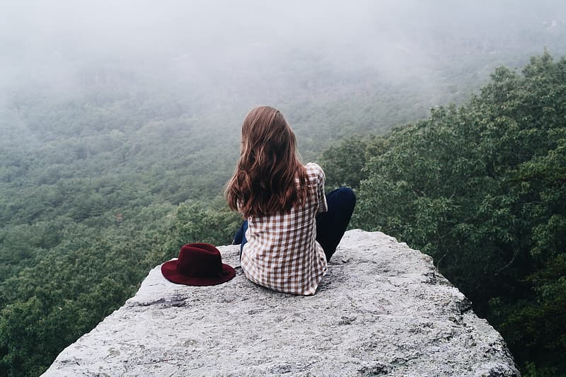 Woman in black and white plaid shirt sitting on gray rock