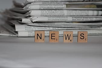 Brown NEWS tiles standing in front of grey piled newspapers