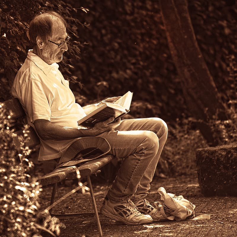 Man sitting on bench while reading book