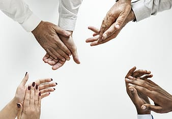 Four person's hand clapping against white background