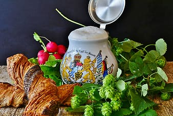 White and blue floral ceramic teapot beside red apple fruit