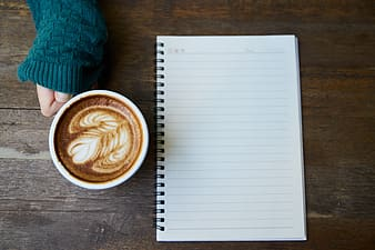 White and black ruled paper and ceramic mug filled with brown coffee