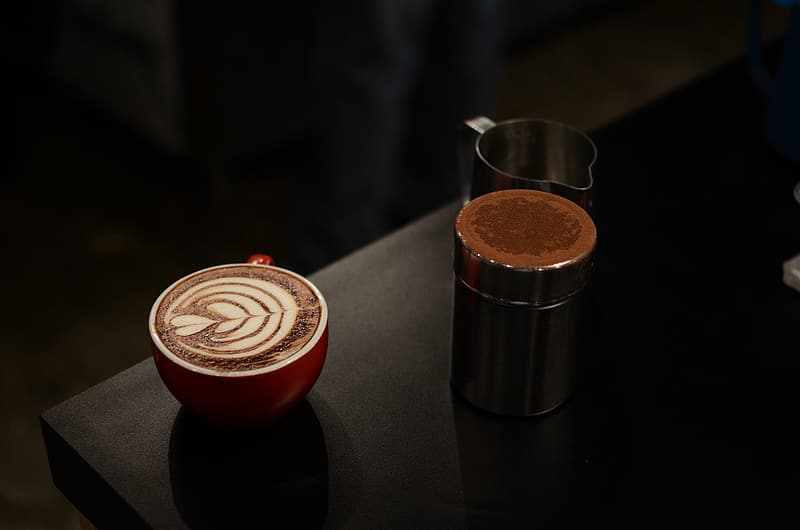 Red and white ceramic cup on black wooden surface